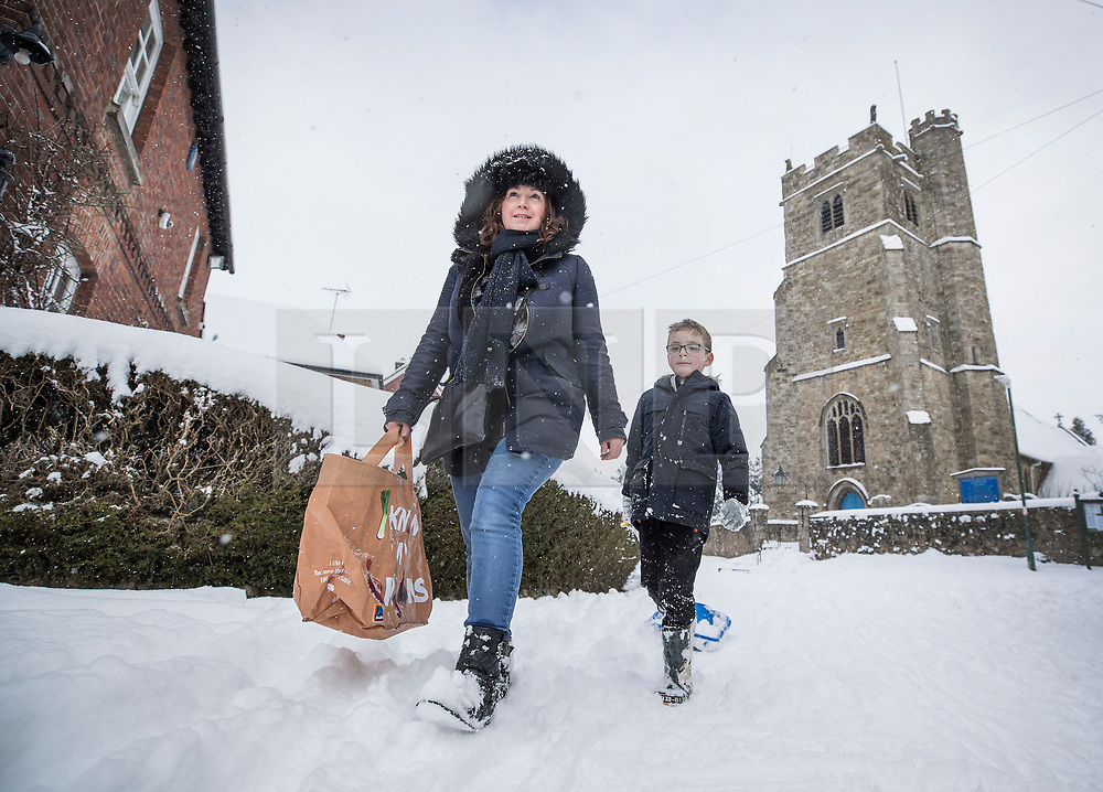 © Licensed to London News Pictures. 27/02/2018. Bearsted, UK. Joanne Dickenson and her son Oliver pass Holy Cross Church in Bearsted, Kent as they head to the shops on foot in heavy snow.. Freezing temperatures and heavy snow are affecting large parts of Kent.  Photo credit: Peter Macdiarmid/LNP