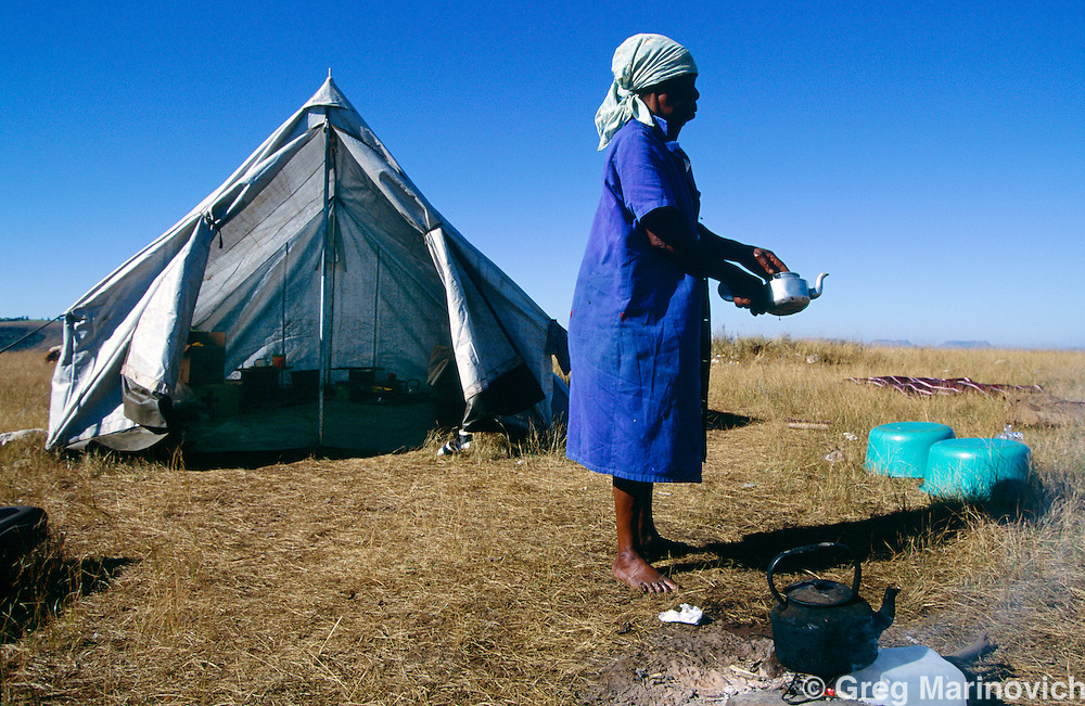 Sonkombo, KwaZulu Natal, 1994, South Africa: A woman packs up at a refugee camp for ANC supporting families from the Sonkombo area from which they had fled months earlier because of attacks by rival IFP. The community was able to retun safely.