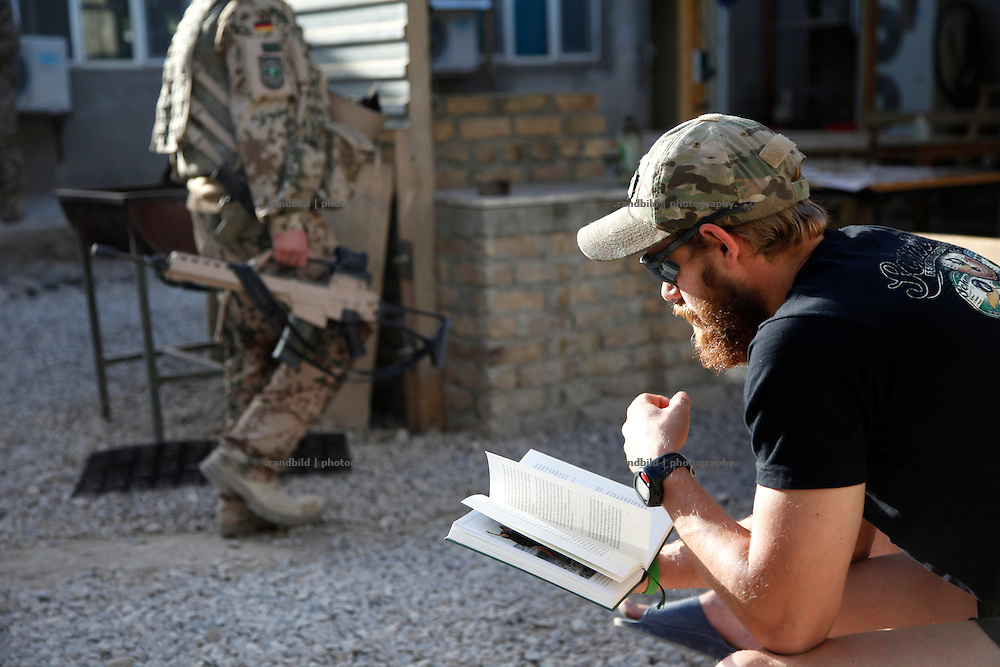 A german soldier reads in the courtyard of District Headquarters, Chahar Dareh, as comrades return combat dressed from a job outside.