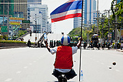 14 MAY 2010 - BANGKOK, THAILAND: An anti-government protester offers water to Thai troops while he waves the Thai flag on Rama IV Rd Friday afternoon. Thai troops and anti government protesters clashed on Rama IV Road Friday afternoon in a series of running battles. Troops fired into the air and at protesters after protesters attacked the troops with rocket and small homemade explosives. Unlike similar confrontations in Bangkok, these protesters were not Red Shirts. Most of the protesters were residents of nearby Khlong Toei slum area, Bangkok's largest slum area. The running battle went on for at least two hours.   PHOTO BY JACK KURTZ