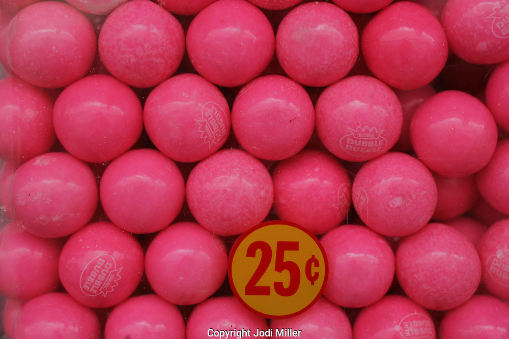 Pink gumballs in a gumball machine.