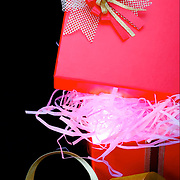 A partially opened boxed and wrapped present with an ornate bow to symbolize a gift. The box is lit from the inside to symbolize mystery and anticipation.