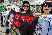 27 AUGUST 2013 - BANGKOK, THAILAND: Protesters line up in front of the main gate into the British embassy grounds in Bangkok. About 25 people, including at least two British citizens, picketed the embassy Tuesday morning. They were protesting against former British Prime Minister Tony Blair, who is expected to speak to a political reform commission established by Thai Prime Minister Yingluck Shinawatra. The protest leaders were invited in to the Embassy grounds to speak to representative of the British government. The protest disbanded afterwards. No one was arrested during the protest, which lasted a little over an hour.       PHOTO BY JACK KURTZ