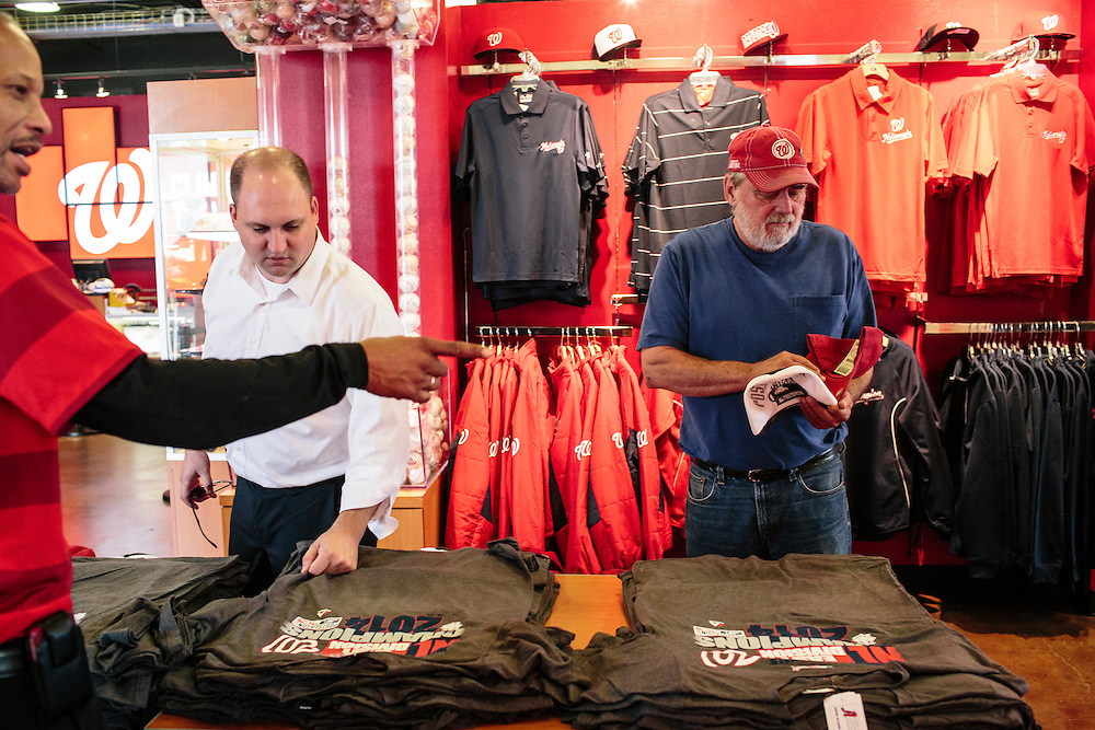 """Bradley Hayes, left, and Jack Berlien, right, look at the post season T-shirts and hats at the Washington Nationals Clubhouse Team Store on Sept. 18, 2014. """"Let's see if we can get past the first round,"""" Berlien, a season ticket holder, said."""