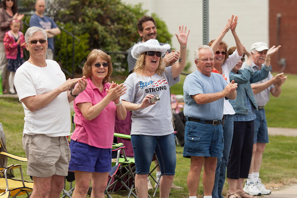 Residents clap as injured Air Force Master Sgt. Joseph Deslauriers Jr. rides past on a float with his wife Lisa in a Memorial Day parade where he served as grand marshall in his home town of Bellingham, MA on Sunday, May 19, 2013. The parade was held a week before the holiday to ensure greater attendance. In 2011, Deslauriers lost both of his legs and part of an arm after stepping on an explosive device while stationed in Afghanistan. He is currently rehabbing at Walter Reed Army Medical Center.  (Matthew Cavanaugh for The Washington Post)
