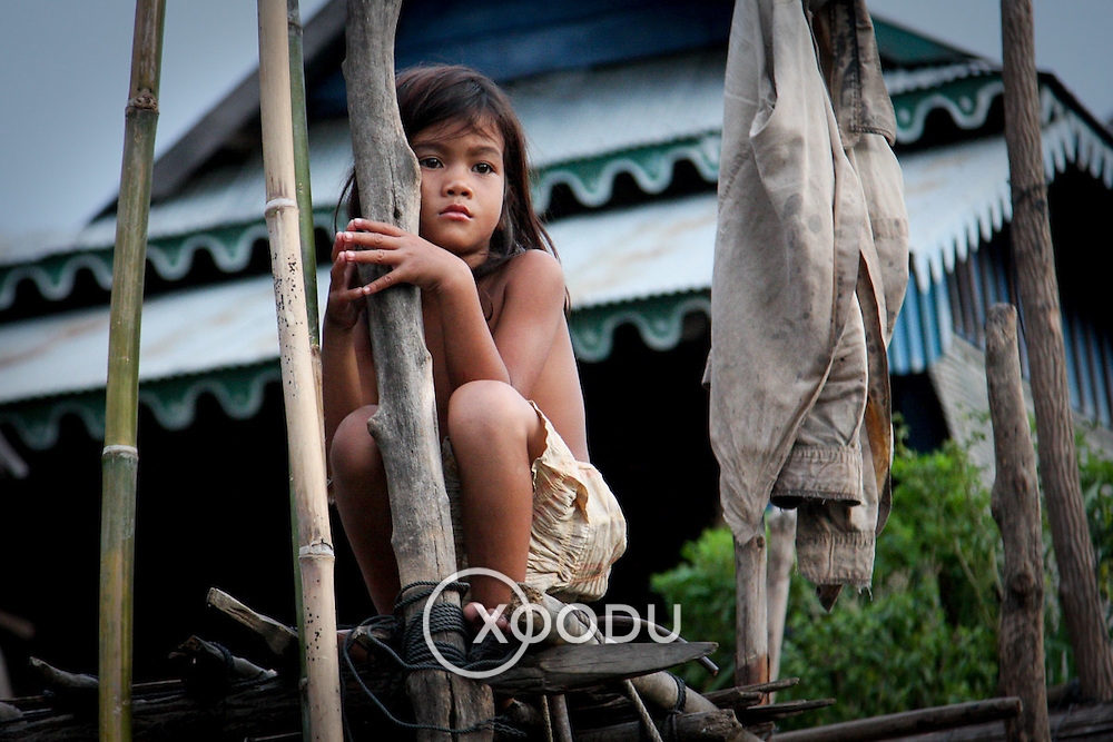 Young girl clinging to wooden pole in fishing village (Siem Reap, Cambodia - Oct. 2008) (Image ID: 081023-1724311a)