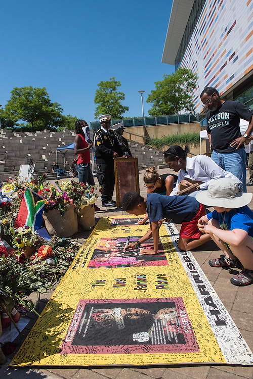 Mourners add their names to a tapestry laid before the makeshift memorial outside of the Muhammad Ali Center as fans, friends honor The Greatest on the plaza outside The Muhammad Ali Center, Thursday, June 9, 2016, in Loiuisville, Ky. (Photo by Brian Bohannon)