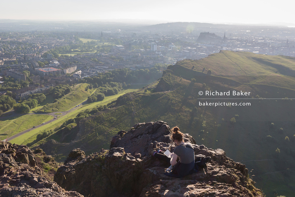 "A young woman works with a notebook in summer evening sunshine on the summit of Arthur's Seat in Holyrood Park, overlooking the city of Edinburgh, on 26th June 2019, in Edinburgh, Scotland. Arthur's Seat is an extinct volcano which is considered the main peak of the group of hills in Edinburgh, Scotland, which form most of Holyrood Park, described by Robert Louis Stevenson as ""a hill for magnitude, a mountain in virtue of its bold design"". The hill rises above the city to a height of 250.5 m (822 ft), providing excellent panoramic views of the city and beyond."