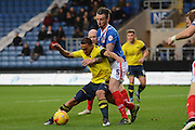 Carlisle United defender Michael Raynes holds up Oxford United midfielder Kemar Roofe during the Sky Bet League 2 match between Oxford United and Carlisle United at the Kassam Stadium, Oxford, England on 12 December 2015. Photo by Alan Franklin.