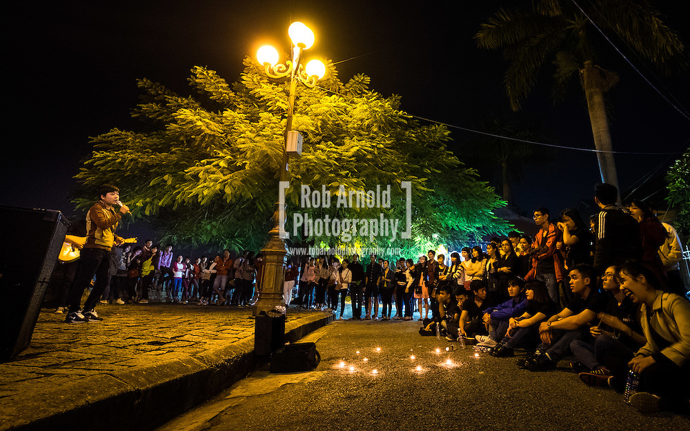 Students taking part in an open mic night on the banks of the Perfume River in Hue, Vietnam