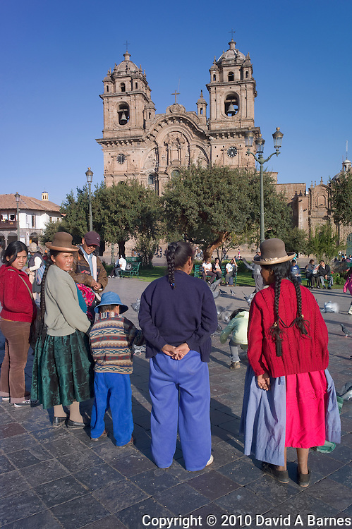 Indigenous family in Plaza de Armes, Church of the Company of Jesus, Cusco, Peru
