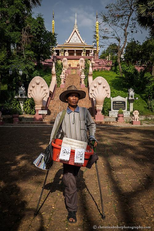 """Ein einbeiniger Kriegsveteran wartet am Fusse des Tempels Wat Phnom auf Touristen, um Postkarten zu verkaufen. Der Wat Phnom ist auf einem 27 Meter hohen, künstlichen Hügel erbaut und ist Namensgeber der Stadt Phnom Penh. Angeblich wurde der Bau der Stupa von Wat Phnom im Jahre 1372 von der wohlhabende Witwe Daun Chi Penh in Auftrag gegeben. Sie gab der Tempelanlage den Namen Wat Phnom Daun Penh. Phnom bedeutet auf Khmer """"Hügel"""". Phnom Penh heisst wortgetreu übersetzt also """"Hügel Penh""""."""