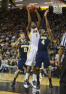 February 19 2011: Iowa Hawkeyes forward Melsahn Basabe (1) puts up a shot over Michigan Wolverines guard Darius Morris (4) as Michigan Wolverines guard/forward Zack Novak (0) looks on during the first half of an NCAA college basketball game at Carver-Hawkeye Arena in Iowa City, Iowa on February 19, 2011. Michigan defeated Iowa 75-72 in overtime.