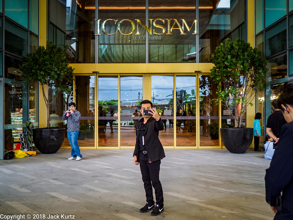 "09 NOVEMBER 2018 - BANGKOK, THAILAND: A man takes a ""selfie"" in front of ICONSIAM before its grand opening Friday. ICONSIAM opened November 9. ICONSIAM is a mixed-use development on the Thonburi side of the Chao Phraya River. It includes two large malls, with more than 520,000 square meters of retail space, an amusement park, two residential towers and a riverside park. It is the first large scale high end development on the Thonburi side of the river and will feature the first Apple Store in Thailand and the first Takashimaya department store in Thailand.     PHOTO BY JACK KURTZ"