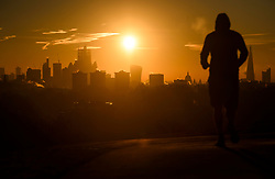 © Licensed to London News Pictures. 03/02/2019. London, UK. A jogger watches the sun rises from behind the City of London, from Primrose Hill in North London on a cold winter morning. Large parts of the UK continue to be deluged with snow and freezing temperatures. Photo credit: Ben Cawthra/LNP