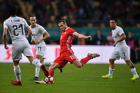 """Gareth Bale, center, of Wales national football team kicks the ball to make a shoot against players of Uruguay national football team in their final match during the 2018 Gree China Cup International Football Championship in Nanning city, south China's Guangxi Zhuang Autonomous Region, 26 March 2018.<br /> <br /> Edinson Cavani's goal in the second half helped Uruguay beat Wales to claim the title of the second edition of China Cup International Football Championship here on Monday (26 March 2018). """"It was a tough match. I'm very satisfied with the result and I think that we can even get better if we didn't suffer from jet lag or injuries. I think the result was very satisfactory,"""" said Uruguay coach Oscar Tabarez. Wales were buoyed by a 6-0 victory over China while Uruguay were fresh from a 2-0 win over the Czech Republic. Uruguay almost took a dream start just 3 minutes into the game as Luis Suarez's shot on Nahitan Nandez cross smacked the upright. Uruguay were dealt a blow on 8 minutes when Jose Gimenez was injured in a challenge and was replaced by Sebastian Coates. Inter Milan's midfielder Matias Vecino of Uruguay also fired at the edge of box from a looped pass but only saw his attempt whistle past the post. Suarez squandered a golden opportunity on 32 minutes when Ashley Williams's wayward backpass sent him clear, but the Barca hitman rattled the woodwork again with goalkeeper Wayne Hennessey well beaten."""
