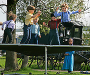 A group of young Amish boys jump on a trampolin at the site of an Amish Auction Saturday along Porter Road in Bonduel, Wi.