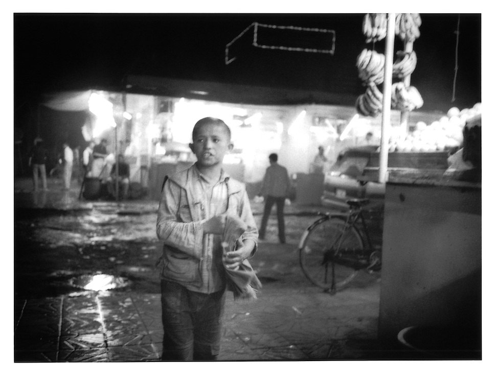 Young boy calls out to customers for a kebab restaurant in Shahr-e Naw, Kabul, Afghanistan.