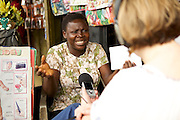 Catherine Raynor, Mile 91, interviewing Esther who runs a party and events decorations company in Nigeria.<br /> <br /> Esther Igwe in her shop 'Goshen Decorates', where she makes and sells decorations for parties and events, Nigeria.<br /> <br /> Esther attended a business training workshop with Youth for Technology and also signed up to receive the business support texts.<br /> <br /> She has learnt a lot from the course and the text messages; including business planning, capital investment, diversifying incomes streams and improving customer relationship management. She says profit is up 40% as a result, that her confidence has improved.<br /> <br /> Esther started her business in 2010 because she had given birth to twins and with her previous three children the family were struggling financially.