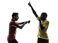 two men soccer player and referee blowing whistle in silhouette on white background