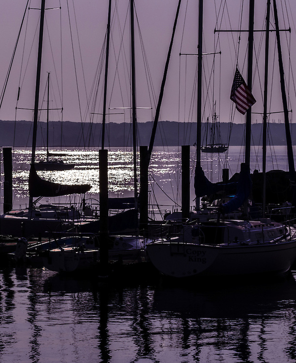 Early morning in East Lyme Connecticut with a purple sunrise and the rigging of moored sailboats in sihouette. An American flag flies from one ship. Light shimmers on the water. Tall ships preparing for the OpSail 2012 parade of sail are seen in the distance near the horizon.