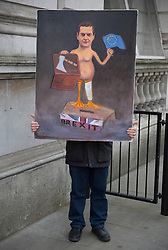 © Licensed to London News Pictures. 16/03/2016. London, UK.  Artist Kaya Mar holds a painting mocking Chancellor of the Exchequer George Osborne on budget day. Photo credit: Peter Macdiarmid/LNP
