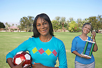 Senior women holding soccer ball and trophy in park, portrait