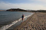 Young girl walks along Sea of Cortez beach at Puerto Gato; Baja, Mexico.