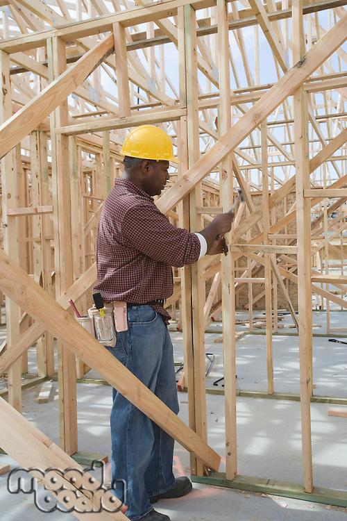 Construction worker hammering framework
