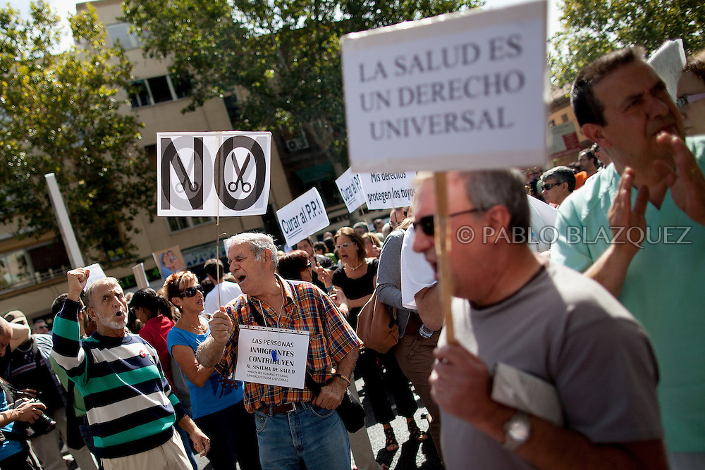 People hold placards outside Gregorio Maranon Hospital as they take part in a demonstration against the Spanish government's latest austerity measures concerning medical care for immigrants, in the center of Madrid, on September 1, 2012. Sign reads 'No Cuts', 'Health care is a universal right'.