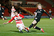 Barnsley defender Ben Williams (28)  is tackled by  Matty Blair of Doncaster Rovers  during the EFL Sky Bet League 1 match between Doncaster Rovers and Barnsley at the Keepmoat Stadium, Doncaster, England on 15 March 2019.