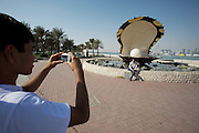 The Pearl Monument in front of the skyline of Western Corniche. Tourists taking souvenir photo.