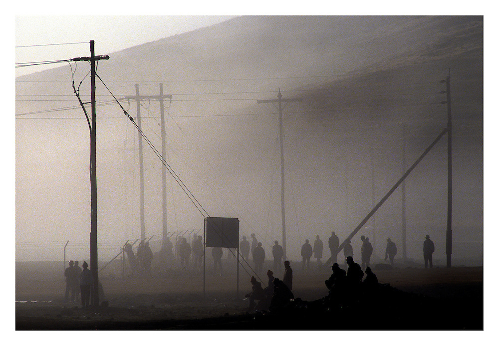 Unemployed men wait outside the perimeter fence in the early morning mist for the chance to work on the Lesotho Highlands Water Project.