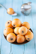 Plate with fresh ripe loquats on wood background.