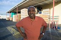 Senior man outside warehouse full of wood