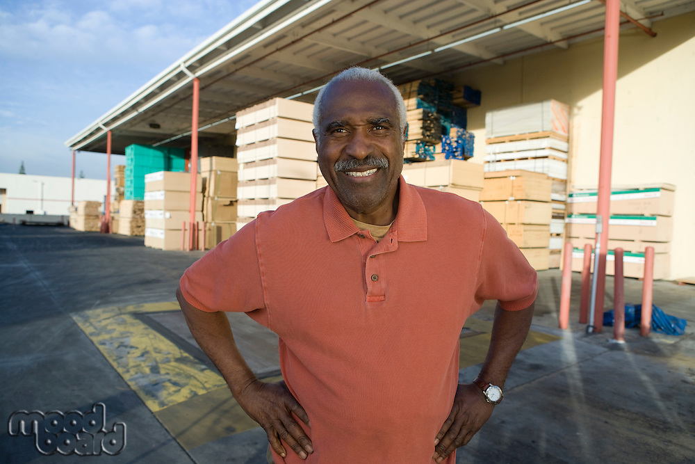 Senior man outside warehouse full of wood