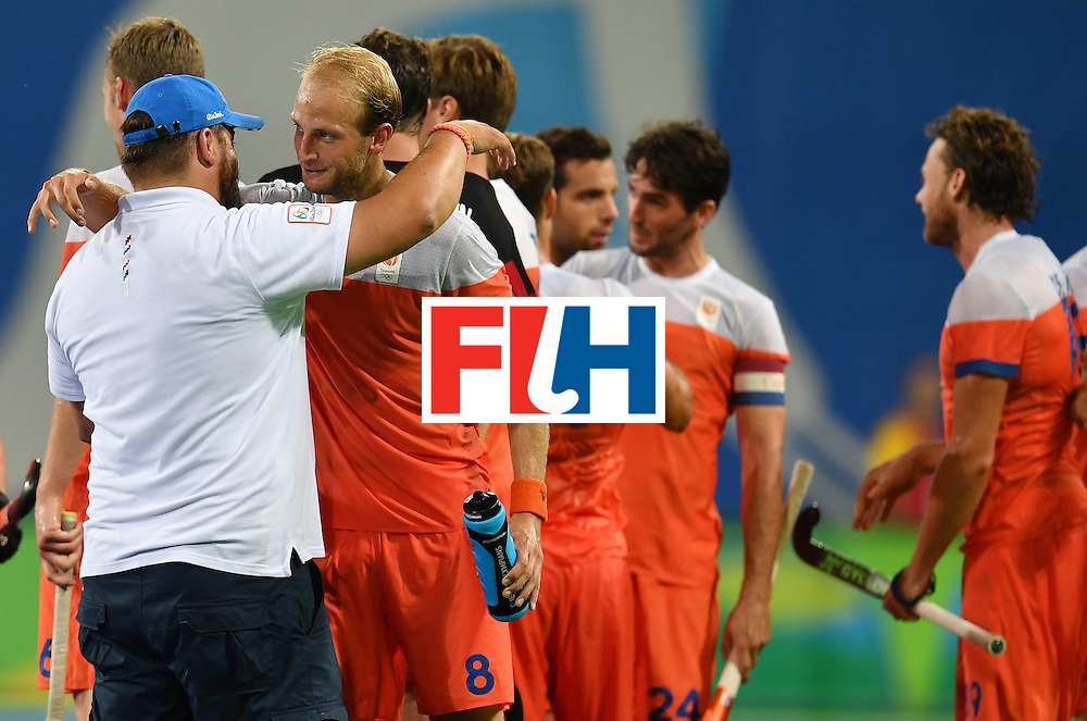 Netherland's coach Max Caldas (L) greets player Billy Bakker at the end of the men's quarterfinal field hockey Netherlands vs Australia match of the Rio 2016 Olympics Games at the Olympic Hockey Centre in Rio de Janeiro on August 14, 2016. / AFP / MANAN VATSYAYANA        (Photo credit should read MANAN VATSYAYANA/AFP/Getty Images)