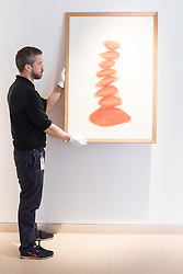 Christies, St James, London, March 4th 2016. A gallery technician hangs David Nash's &quot;Column&quot;, pastel on paper, created especially for the auction at the preview for the It&rsquo;s Our World charity auction at Christie's. Over 40 leading artists including David Hockney, Sir Antony Gormley, David Nash, Sir Peter Blake, Yinka Shonibare, Sir Quentin Blake, Emily Young and Maggi Hambling have committed artworks to the It&rsquo;s Our World Auction in support of The Big Draw and Jupiter Artland Foundation, to be sold at Christie&rsquo;s London on 10 March 2016.<br />  ///FOR LICENCING CONTACT: paul@pauldaveycreative.co.uk TEL:+44 (0) 7966 016 296 or +44 (0) 20 8969 6875. &copy;2015 Paul R Davey. All rights reserved.