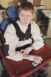 Young boy with Cerebral Palsy sitting in wheelchair on Children's ward in hospital; holding toy car and looking anxious,