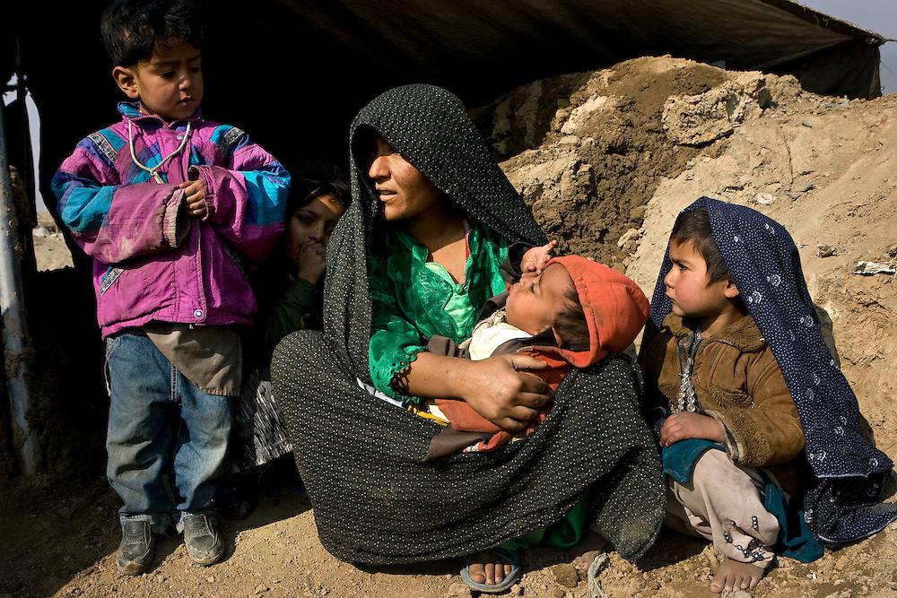 Womenfolk and children displaced by violence and Taliban intimidation in the area around Musa Qala in Afghanistan's troubled Helmand Province prepare to spend the freezing winter living in tents in a makeshift refugee camp on the outskirts of Kabul, Afghanistan on the 13th December 2007.