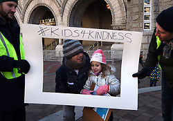"""December 10, 2016 - Washington, DC, USA - ELSIE KARLINS, 5 years old, and her father ERIC KARLINS have their picture taken inside frame of ''Photo Booth''.  Holding sign is SAM REGGIO, right, and LOGAN WORSLEY, left.   Children's Rally for Kindness takes place at Trump International Hotel in Washington DC on December 10, 2016 organized by the Takoma Parents Action Coalition.  According to their FaceBook page, it was a call to President-elect Donald Trump: ''to remember these lessons as he prepares to take office and implement policies that will affect the lives of children and families across our diverse nation.''.''All over the world, across cultures and countries, children learn the same basic lessons: .Ã'be kind,Ã"""" .Ã'tell the truth,Ã"""" .Ã'be fair,Ã"""" .Ã'respect everyone,Ã"""" .Ã'treat others the way you want to be treated,Ã"""" .Ã'donÃ•t touch others if they donÃ•t want to be touched. (Credit Image: © Carol Guzy via ZUMA Wire)"""