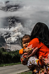 January 3, 2018 - Karo, North Sumatra, Indonesia - Indonesian women with his daughter as Mount Sinabung spews thick smoke in Karo, North Sumatra. Mount Sinabung roared back to life in 2010 for the first time in 400 years, after another period of inactivity it erupted once more in 2013, and has remained highly active since. (Credit Image: © Ivan Damanik via ZUMA Wire)