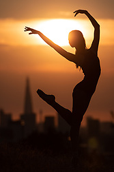© Licensed to London News Pictures. 24/07/2018. London, UK. Royal Ballet dancer Sae Maeda performs a ballet pose as the sun sets over London's skyline, after temperatures in the South East of England reached over 30 degrees celsius today. Temperatures are set to rise up to 35 degrees on Thursday, as the UK experiences a prolonged heatwave. Photo credit : Tom Nicholson/LNP