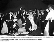 Ballgoers throwing eggs at gatecrasher in stocks during Magdalene May Ball. June 1983. Film 83415f11<br />