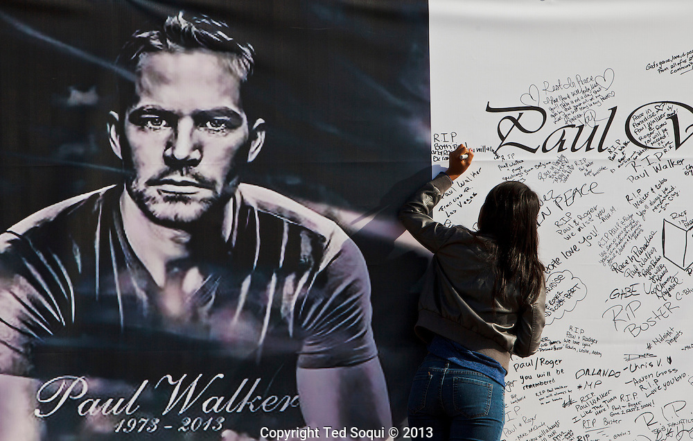 Friends and fans of Paul Walker and Roger Rodas sign a giant banner.<br /> An informal street memorial for Paul Walker, key actor in the &quot;Fast and Furious&quot; film enterprise, and Roger Rodas, race car driver, who were both killed in a solo car auto accident in Valencia, CA. The memorial was held at the crash site, and featured several cars Paul Walker drove in the &quot;Fast and Furious&quot; films. Thousands of fans and car enthusiast showed up to pay their respects.
