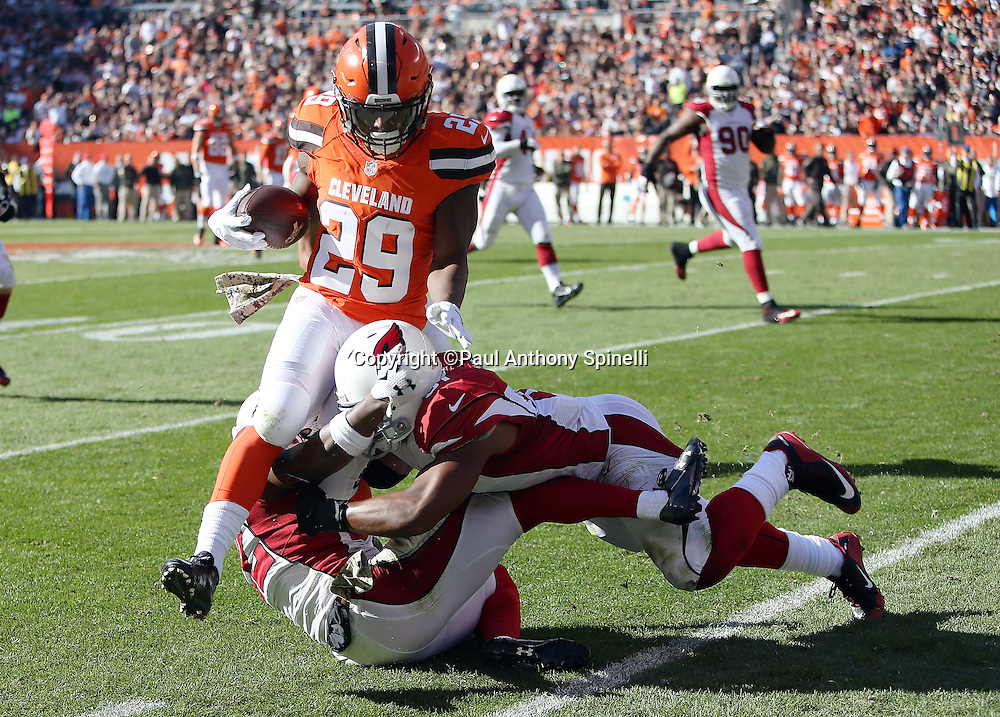 Cleveland Browns running back Duke Johnson, Jr. (29) gets gang tackled by Arizona Cardinals strong safety Tony Jefferson (22) and Arizona Cardinals middle linebacker Kevin Minter (51) as he runs with the ball after catching a second quarter pass for a 16 yard gain at the Arizona Cardinals 30 yard line during the 2015 week 8 regular season NFL football game against the Arizona Cardinals on Sunday, Nov. 1, 2015 in Cleveland. The Cardinals won the game 34-20. (©Paul Anthony Spinelli)