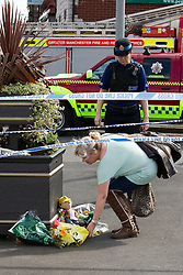 © Licensed to London News Pictures. 27/06/2012. Oldham , UK . A large explosion , believed to be caused by gas , has brought down at least one house in an Oldham terrace. A woman lays flowers by a makeshift shrine dedicated to 2 year old Jamie Heaton who was killed in the blast . Photo credit : Joel Goodman/LNP