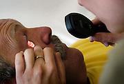 Nederland, Nijmegen, 11-7-2005..Een arts, huisarts, van de huisartsenpost, huisartsendienst, kijkt in het oog van een patient waar vuil in is gekomen. Onderzoek. Oogletsel, oogbeschadiging. Avonddienst, bereikbaarheid, spoedgeval, ongelukje, steengruis, steen hakken. Gezondheidszorg, eerstelijnszorg...Foto: Flip Franssen