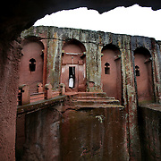 A priest in the doorway of Bet Gabriel-Rafael church in Lalibela. Lalibela's churches are in carved out of red volcanic stone. Bet Gebriel-Rafael has a plunging facade. Christianity came to Ethiopia in the 4th century and the Ethiopian Orthodox Church has retained its own unique traditions.