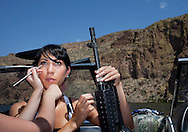 Tiffany Webb has makeup applied by artist Caityn Vaughn at Canyon Lake.  Webb was photographed holding an FN M240B machine gun for the 2012 Coleman Tyler LLC calendar.